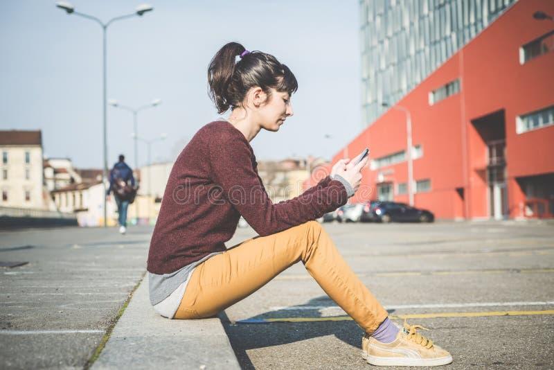 Jonge mooie hipstervrouw die slimme telefoon met behulp van royalty-vrije stock afbeelding