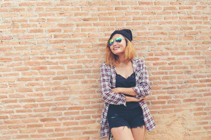 Jonge mooie hipstervrouw die zich tegen bakstenen muur bevinden die sm stellen royalty-vrije stock foto