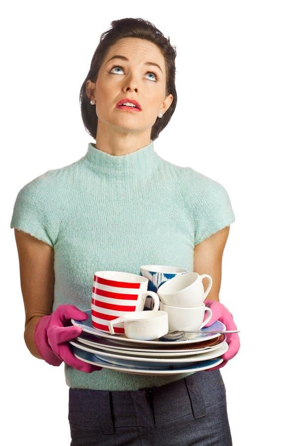 Jonge mooie huisvrouw met stapel van schotels stock afbeelding