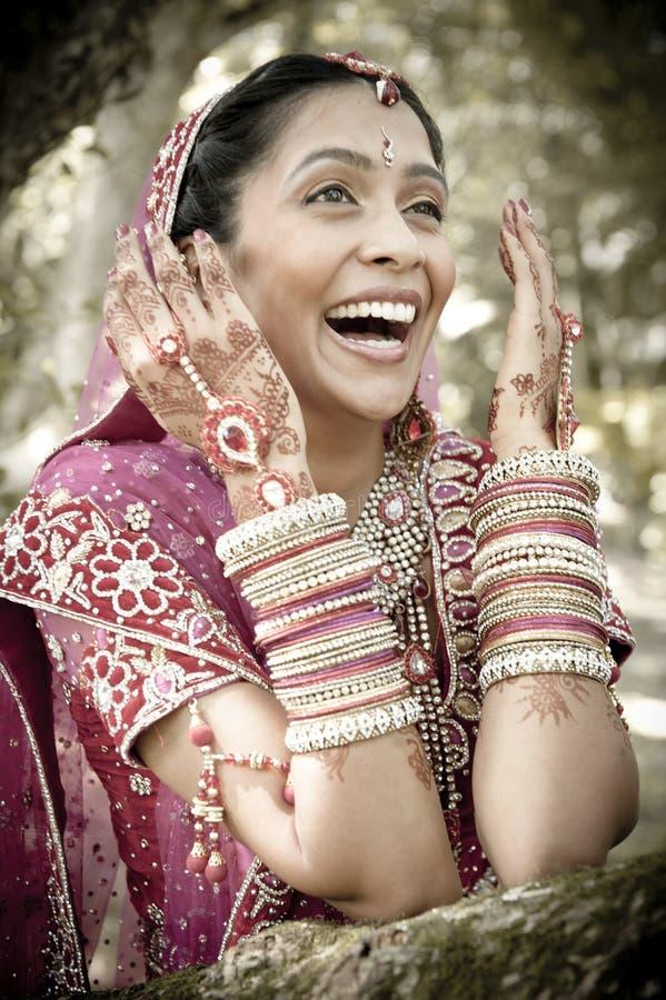 Jonge mooie Indische Hindoese bruid die onder boom met geschilderde opgeheven handen lachen stock afbeeldingen