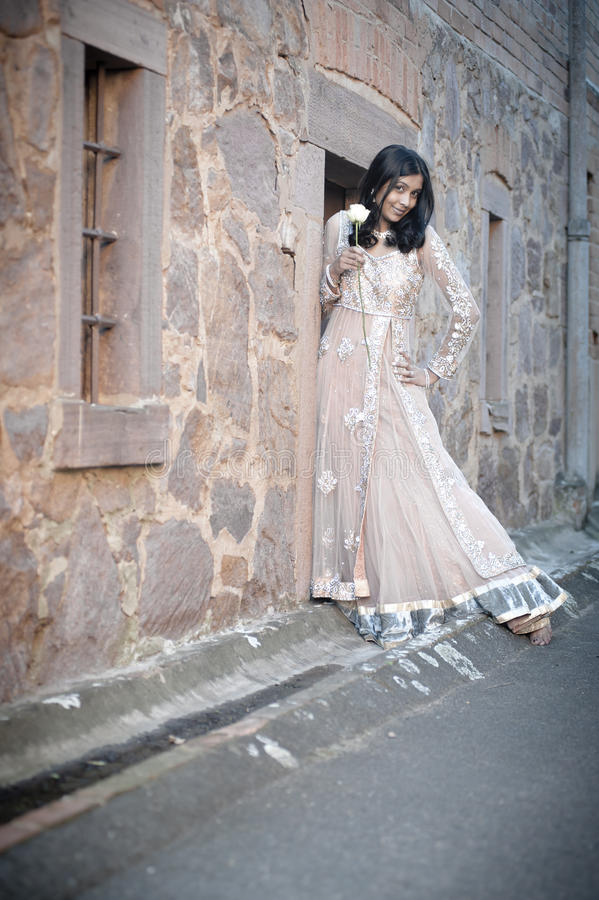 Jonge mooie Indische Vrouw die tegen steenmuur zich in openlucht bevinden royalty-vrije stock fotografie