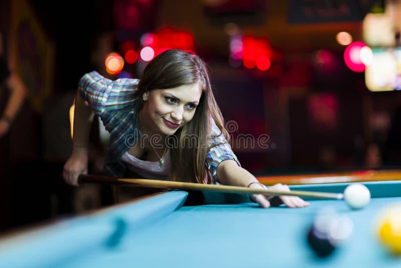 Jonge mooie jonge dame die het snookerschot pogen te nemen royalty-vrije stock afbeelding