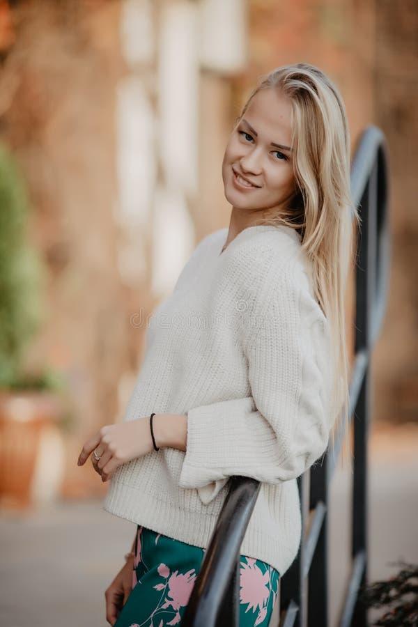 Jonge mooie Kaukasische blondevrouw openlucht in stads achterlicht, die op leuning leunen stock foto