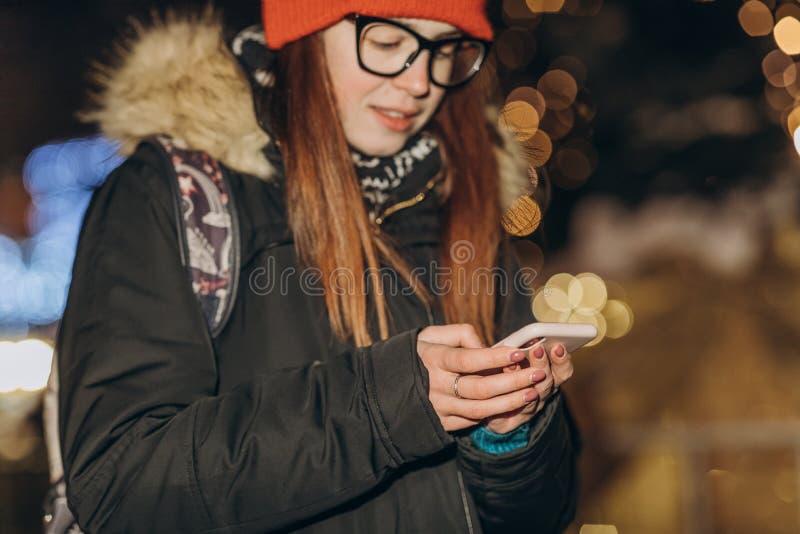 Jonge mooie Kaukasische vrouw die de greep van de smartphonehand openlucht in de stadsnacht gebruiken stock foto