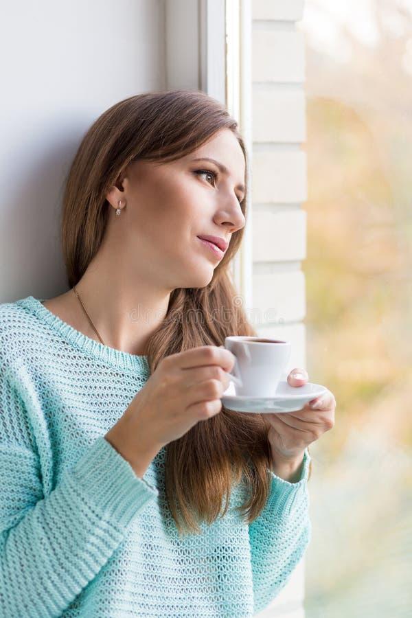Jonge mooie Kaukasische vrouw die haar espresso drinken bij venstervensterbank stock fotografie