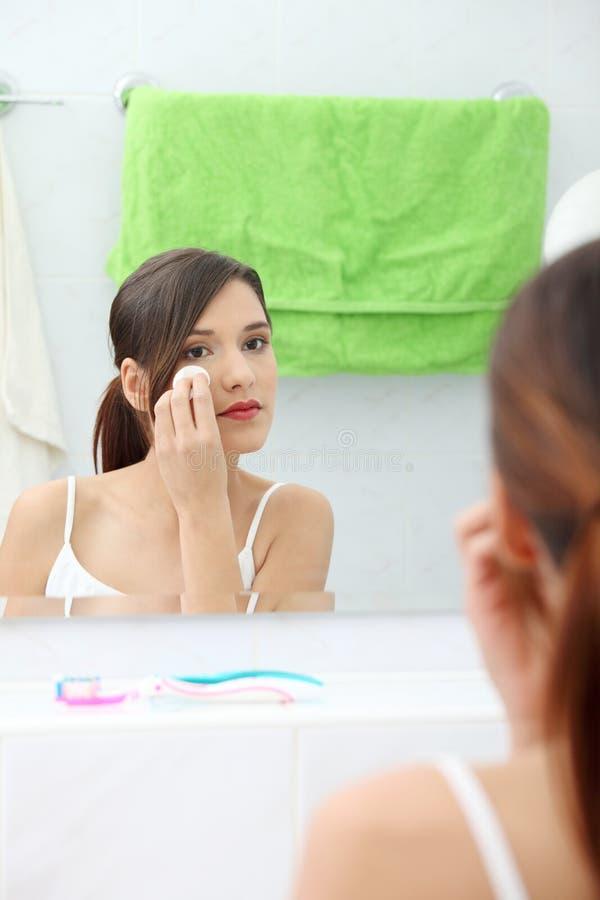 Jonge mooie Kaukasische vrouw die haar gezicht schoonmaakt royalty-vrije stock afbeeldingen