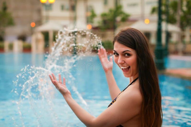 Jonge mooie Kaukasische vrouw die waterplons maken bij de pool die van de zomer genieten Vakantiestemming stock foto's