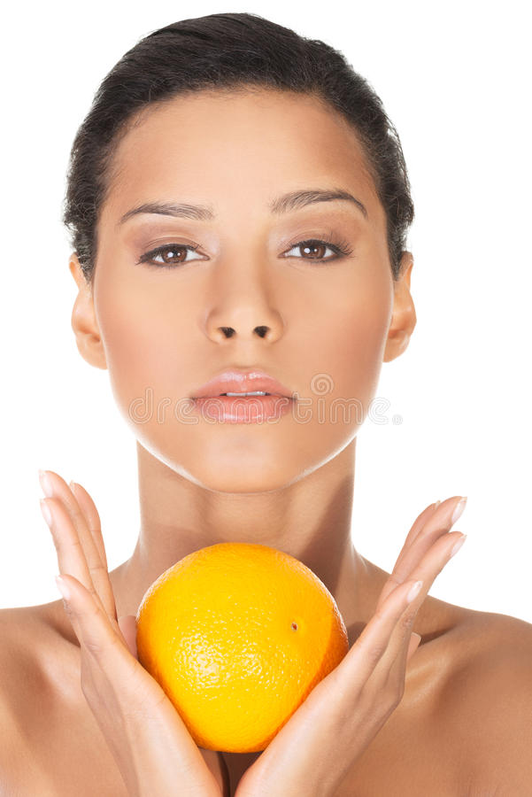 Jonge mooie kuuroordvrouw met sinaasappel in haar hand royalty-vrije stock foto's