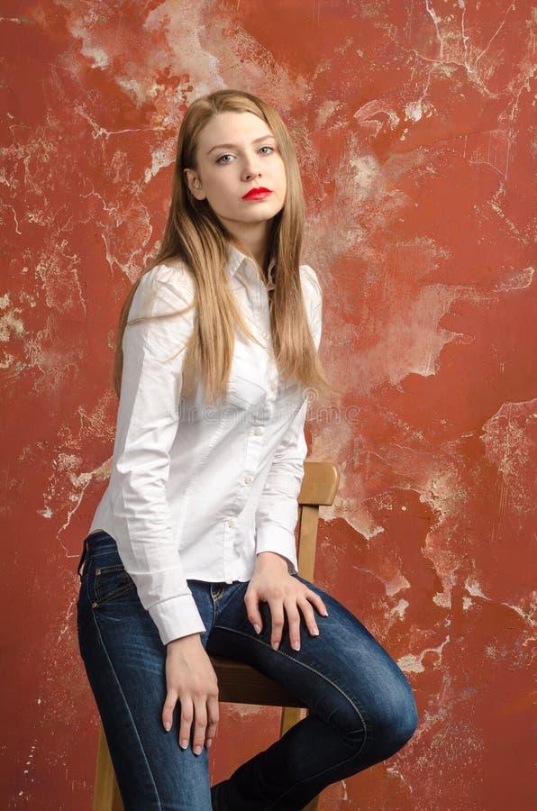 Jonge mooie langharige bruin-haired vrouw in losgeknoopte witte overhemd en jeans royalty-vrije stock fotografie