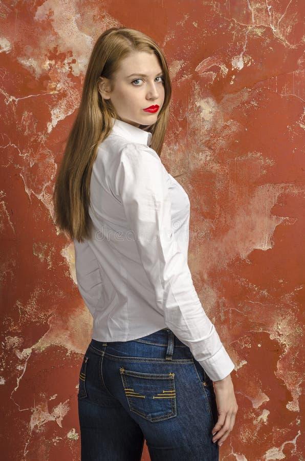 Jonge mooie langharige bruin-haired vrouw in losgeknoopte witte overhemd en jeans royalty-vrije stock afbeeldingen