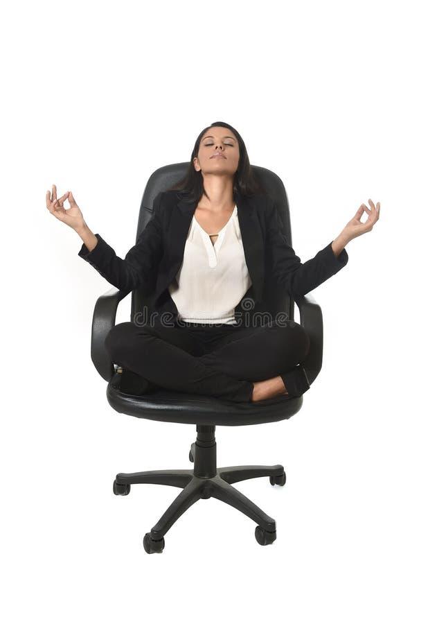 Jonge mooie Latijns-Amerikaanse bedrijfsvrouwenzitting bij bureaustoel in lotusbloemhouding het praktizeren yoga royalty-vrije stock afbeeldingen