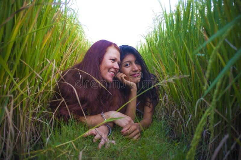 Jonge mooie Latijnse vrouw en haar aantrekkelijk rood haarmeisje beide meisjes die de Zomer van vakantie samen op padieveld genie stock foto's