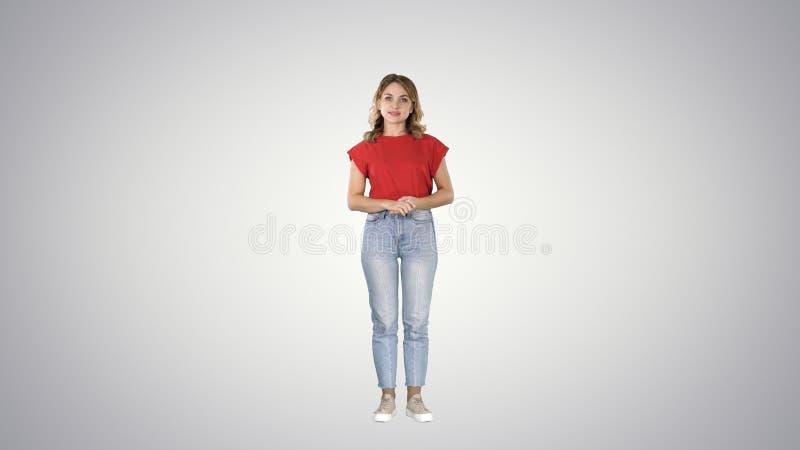 Jonge mooie leuke vrolijke vrouw die en zich camera bevinden bekijken die op iets op gradiëntachtergrond wachten royalty-vrije stock fotografie