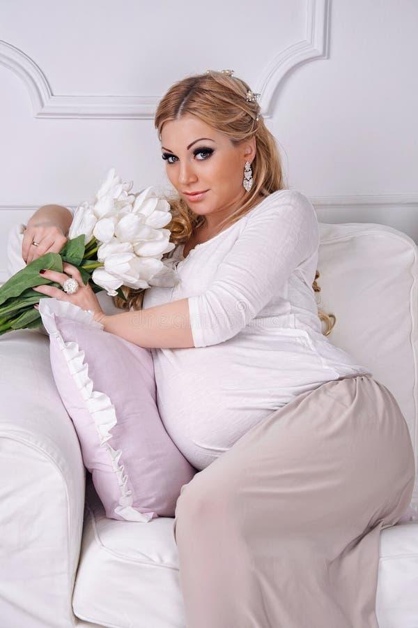 Jonge mooie manier zwangere vrouw op een wit stock afbeelding