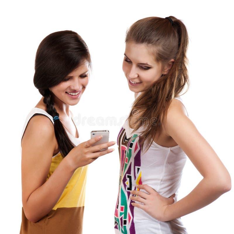 Jonge mooie meisjes die cellphone gebruiken om te verzenden en te ontvangen sms royalty-vrije stock foto