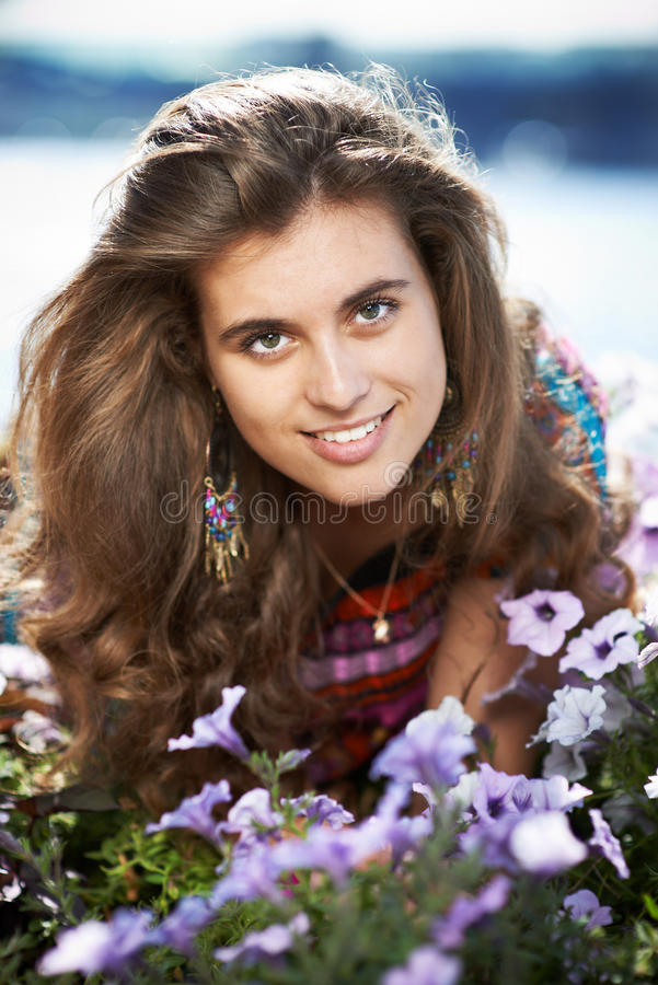 Jonge mooie meisjes volgende deur met purpere bloemen royalty-vrije stock afbeelding
