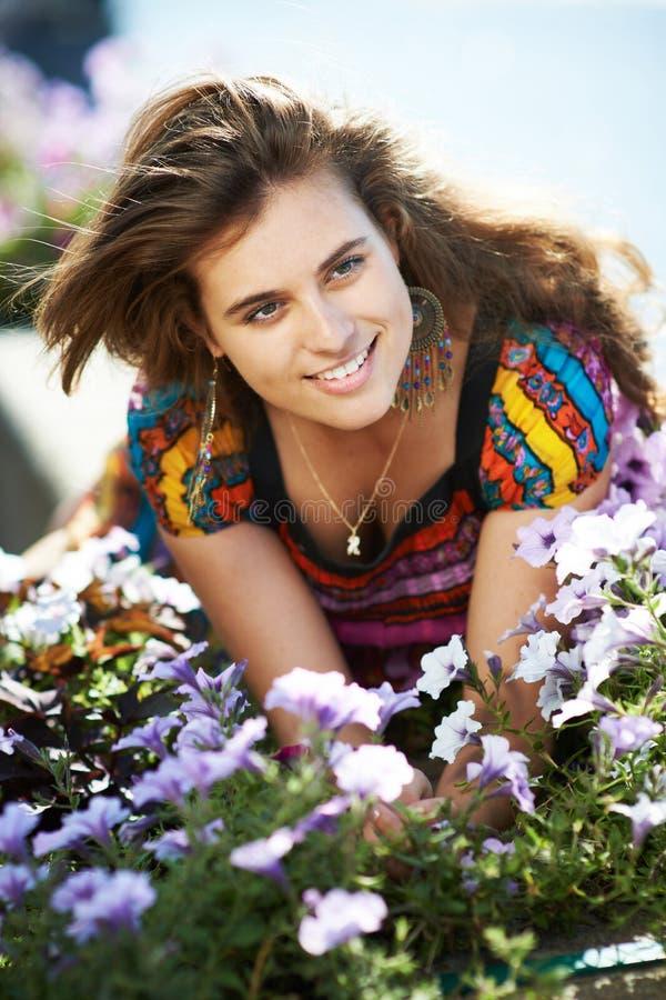 Jonge mooie meisjes volgende deur met purpere bloemen stock foto
