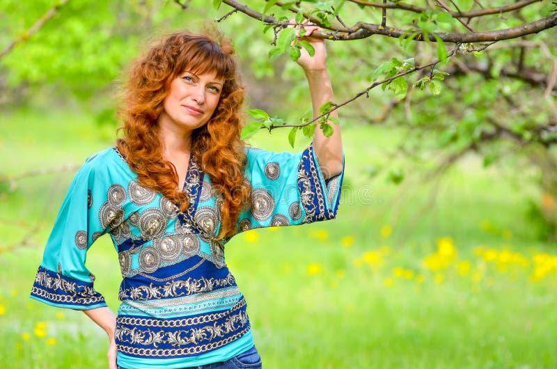 Jonge mooie meisjesgangen in de boomgaard van de de lente groene appel stock fotografie