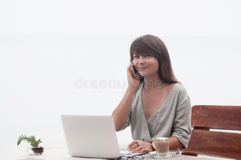 Jonge mooie meisjeszitting in een koffiewinkel met laptop en het spreken op pnone stock foto