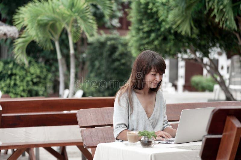 Jonge mooie meisjeszitting in een koffiewinkel in openlucht en werkend aan computer stock afbeelding