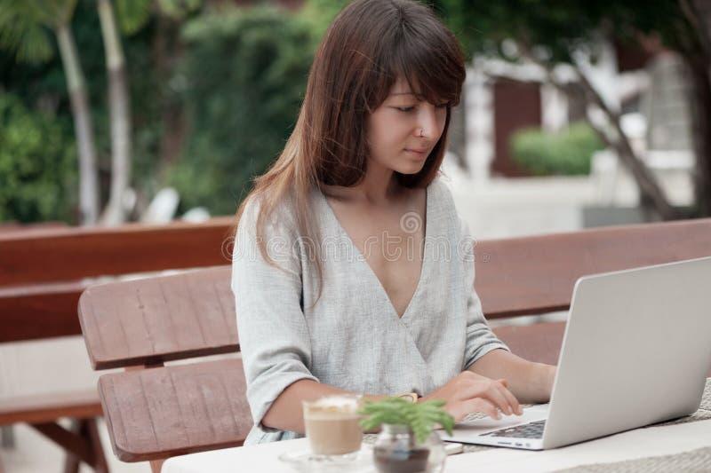 Jonge mooie meisjeszitting in een koffiewinkel in openlucht en werkend aan computer royalty-vrije stock fotografie