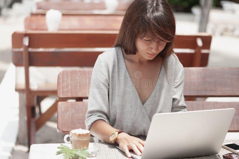 Jonge mooie meisjeszitting in een koffiewinkel in openlucht en werkend aan computer stock fotografie