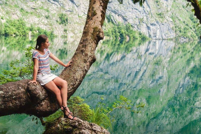 Jonge mooie meisjeszitting op een boom op Obersee-meer met duidelijk groen water stock foto
