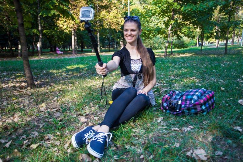 Jonge mooie meisjeszitting op gras en het nemen selfie op een actiecamera royalty-vrije stock afbeelding