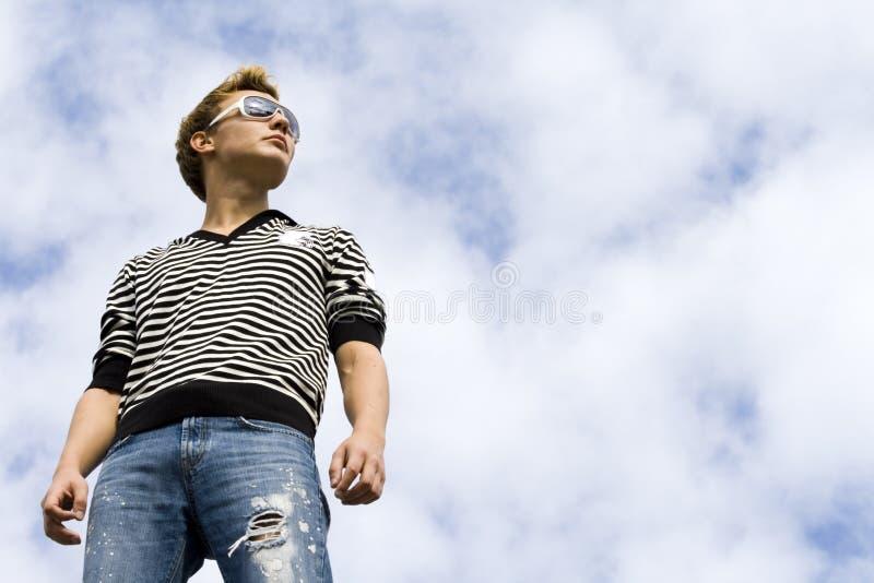Jonge mooie mens model status onder de wolk royalty-vrije stock fotografie
