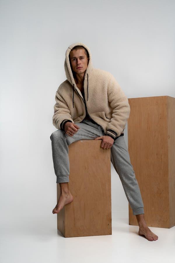 Jonge mooie mens in modieuze sportkledingszitting op houten kubus, die de camera bekijken over witte achtergrond wordt ge?soleerd royalty-vrije stock fotografie