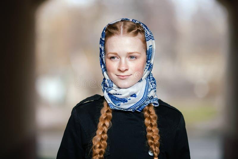Jonge mooie modieuze roodharigevrouw met vlechtenkapsel in blauw wit zwart de geuljasje die van het headcraft modieuze denim outd stock foto