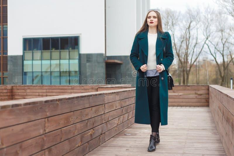 Jonge mooie modieuze vrouw die onderaan straat in smaragdgroene laag en witte gebreide sweater lopen royalty-vrije stock fotografie