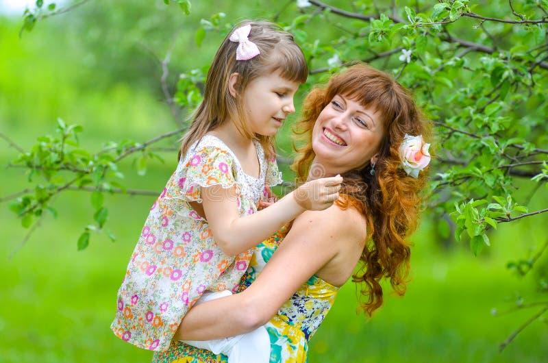Jonge mooie moeder die met haar dochter in de tuin lopen royalty-vrije stock foto's