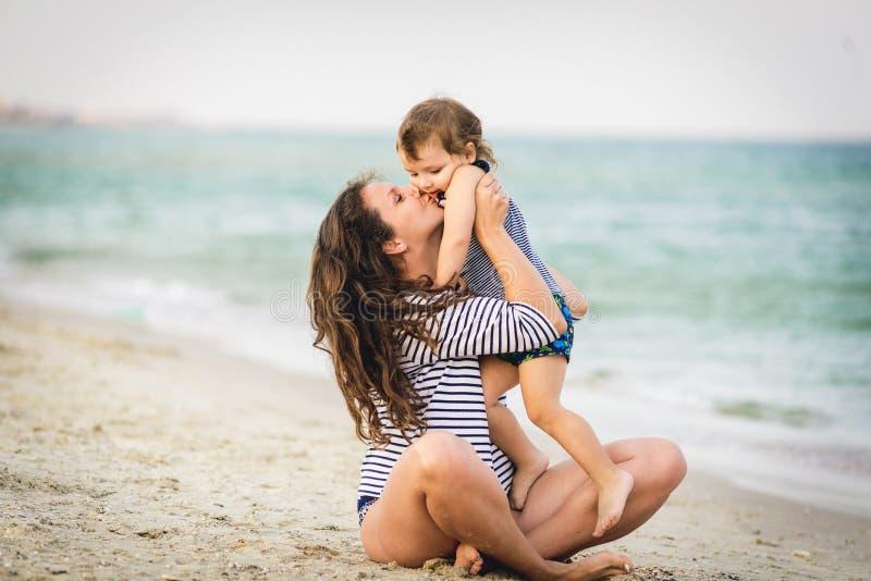 Jonge mooie moeder en haar aanbiddelijke zoon die pret op het strand hebben royalty-vrije stock afbeelding