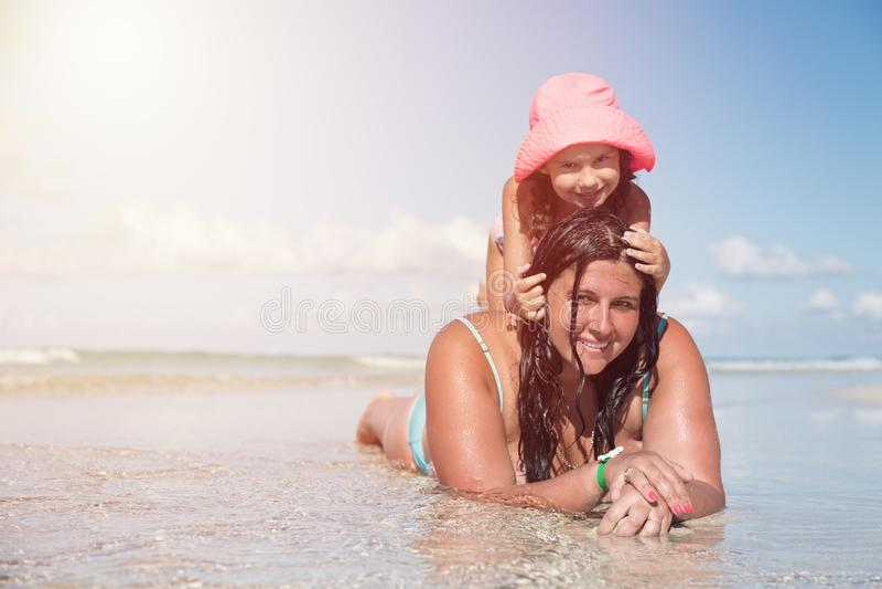 Jonge mooie moeder en haar meisje in roze hoed die van de oceaan genieten en bij het tropische strand tijdens zonnige dag ontspan stock afbeeldingen