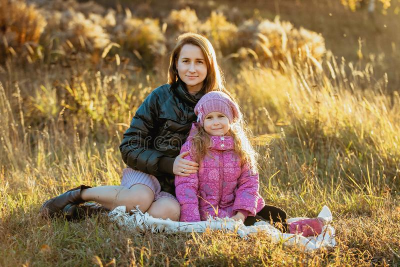 Jonge mooie moeder met haar dochter op een gang op een zonnige de herfstdag Zij zitten op een plaid op het gras dicht bij elk o stock foto's