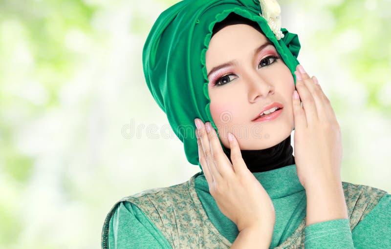 Jonge mooie moslimvrouw met groen kostuum die hijab dragen stock foto
