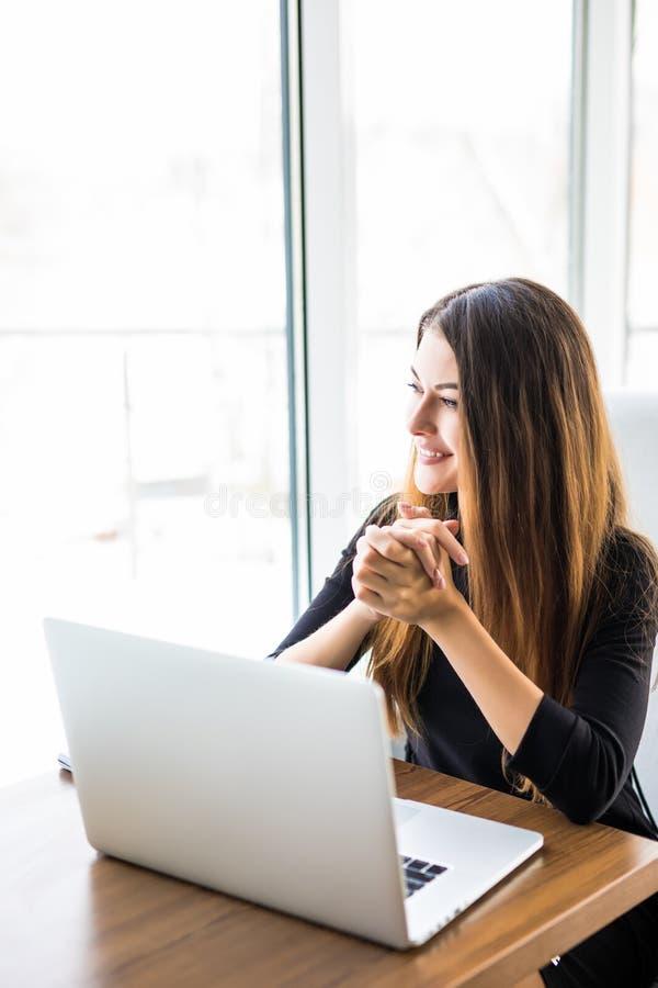 Jonge mooie onderneemster die aan laptop werken en hand op kin houden terwijl het zitten op haar werkende plaats stock fotografie