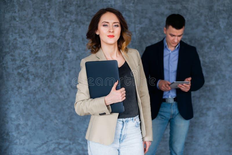 Jonge mooie onderneemster die een laptop computer op commerciële vergadering houdt stock foto's