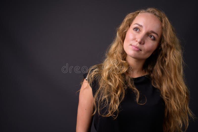 Jonge mooie onderneemster met het lange golvende blonde haar denken stock foto's