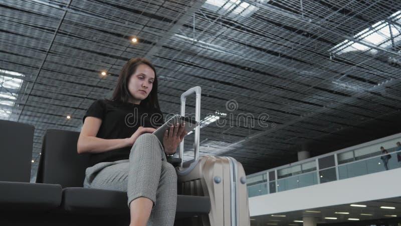 Jonge Mooie Onderneemster Using een Tabletpc bij Luchthaven terwijl het Wachten van Haar Rij op Registratie, die Concept reizen royalty-vrije stock afbeeldingen