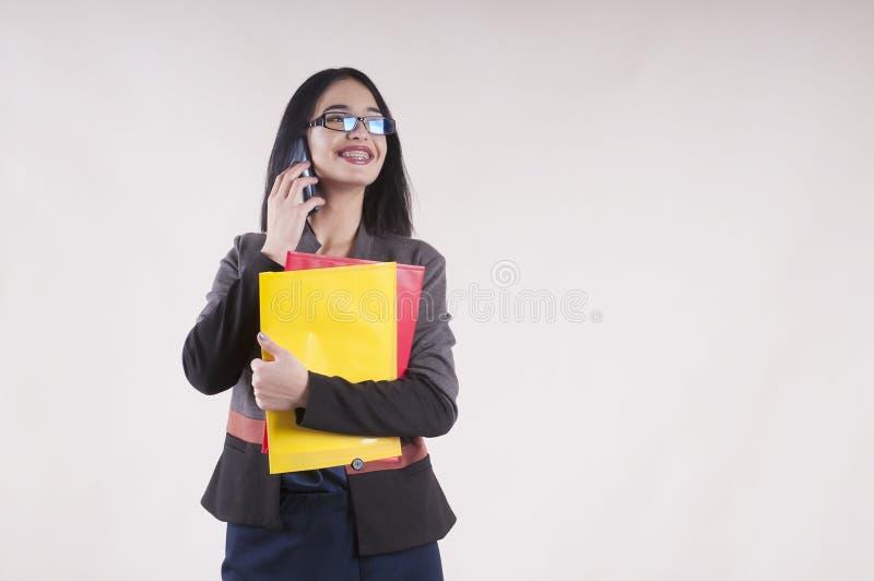 Jonge mooie onderneemstertelefoon het glimlachen steunen rode en gele omslagglazen royalty-vrije stock foto