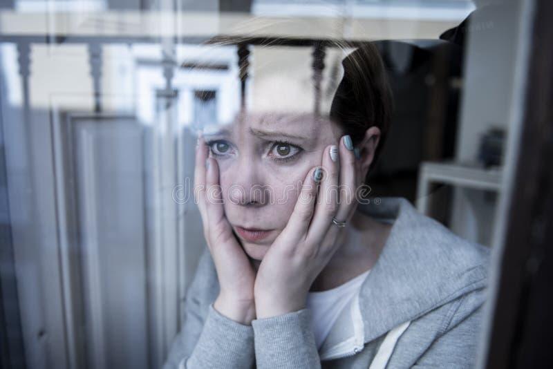 Jonge mooie ongelukkige gedeprimeerde eenzame vrouw kijken die die door het venster thuis wordt gefrustreerd stock foto's