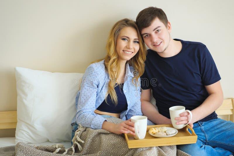 Jonge mooie paar het drinken koffie in bed bij ochtend, royalty-vrije stock afbeelding
