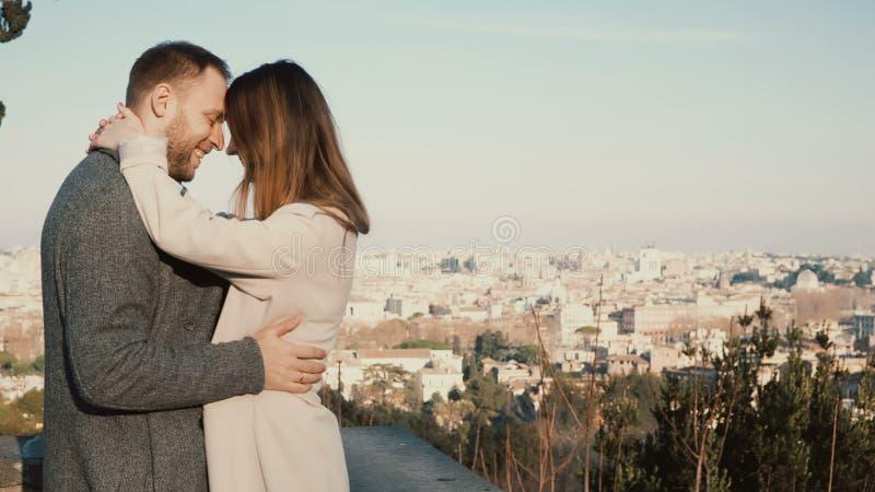 Jonge mooie paaromhelzing en kus tegen het panorama van Rome, Italië Romantische datum van de gelukkige mens en vrouw royalty-vrije stock afbeeldingen