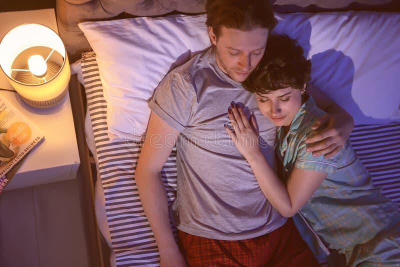 Jonge mooie paarslaap in bed stock afbeeldingen