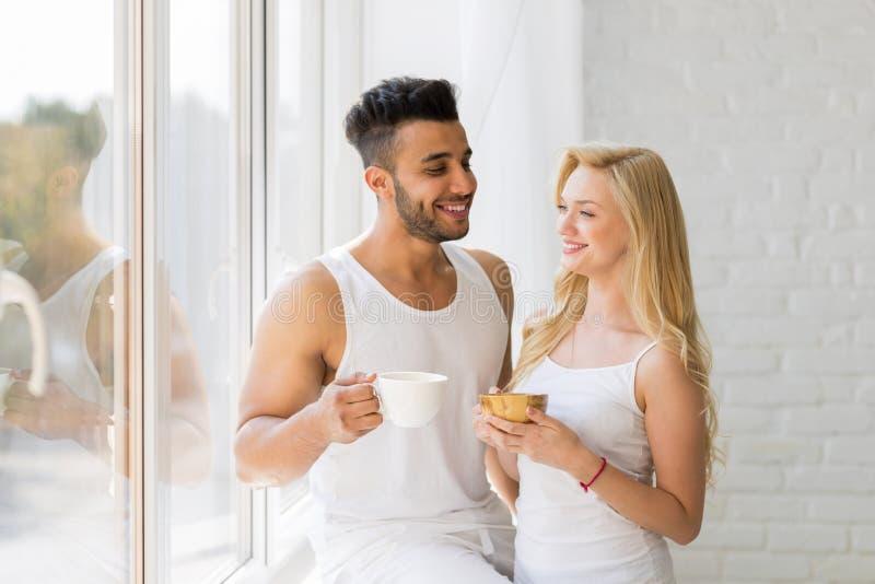 Jonge Mooie Paartribune dichtbij Groot Venster, de Koffiekop van de Drankochtend, de Gelukkige Glimlach Spaanse Mens en Vrouw royalty-vrije stock foto