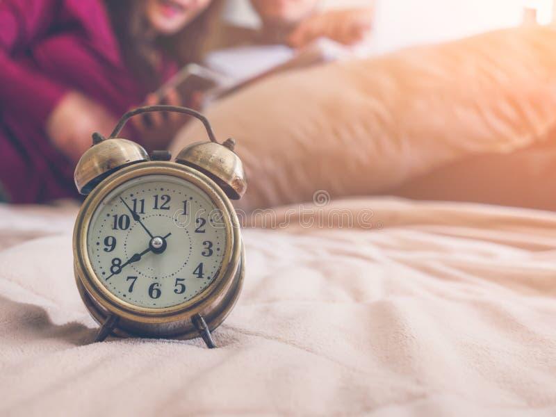 Jonge mooie paarzitting in bed, gebruiken mobiel voor het winkelen in vrije tijd in de ochtend Alamklok op rand van het bed Nadru stock afbeeldingen