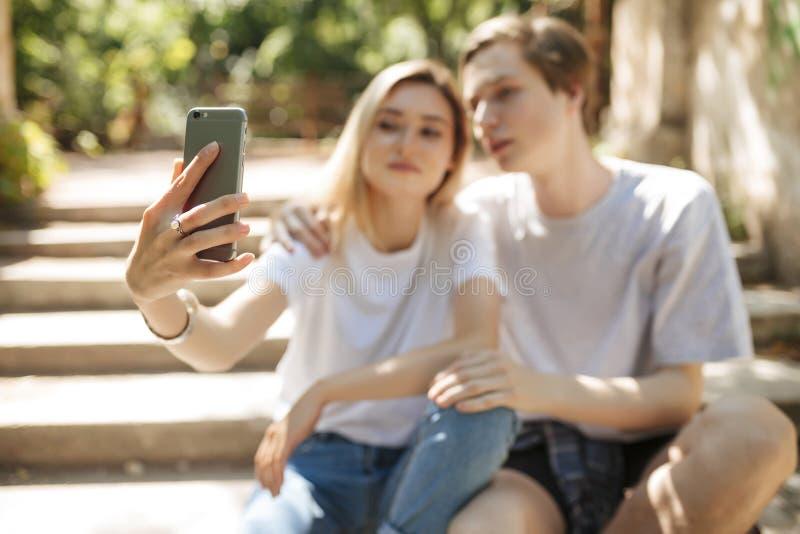 Jonge mooie paarzitting en het maken selfie Sluit omhoog foto van vrouwenhand die mobiele telefoon houden en foto overnemen stock foto
