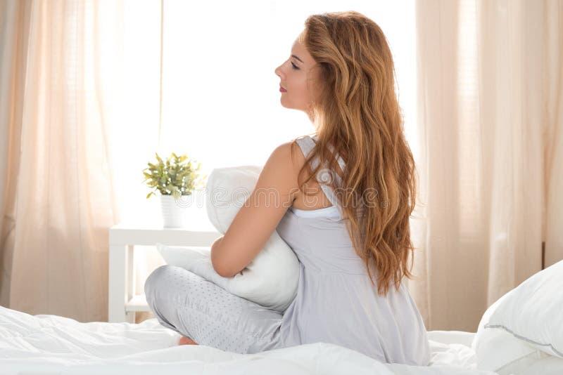 Jonge mooie peinzende vrouwenzitting op haar bed en holding haar stock foto